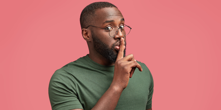 Man in glasses putting finger to his mouthMan in glasses putting finger to his mouth 840x420