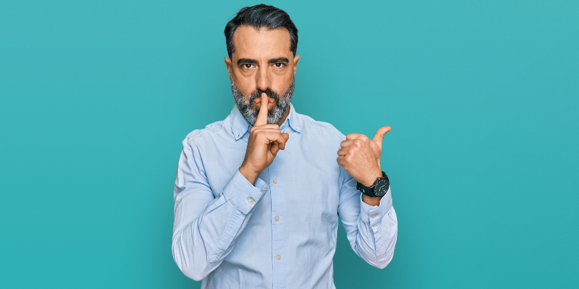 Man in blue shirt putting finger to his mouth