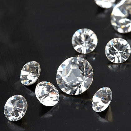brilliant diamond placed on dark and reflective surface