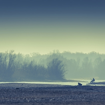 fisherman on dusty and rainy day sitting at the river