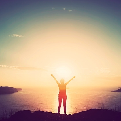woman with hands up standing on cliff over sea and islands at sunset
