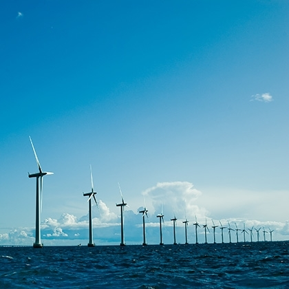 row of windmills standing in the sea against blue sky