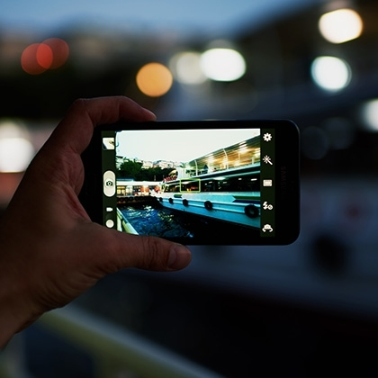 person taking a photo of touristic sail boat using smartphone camera