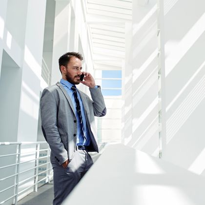 Man on telephone standing outside an office balcony
