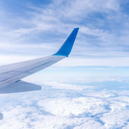 aeroplane wing in blue clouded sky