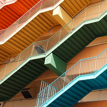 Colorful stairs in front of orange building: фотография