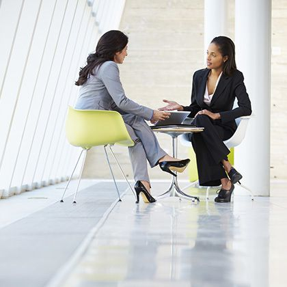 two businesswomen meeting around table in modern and bright office