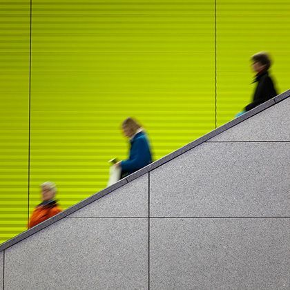 commuters on escalator against green background copy space