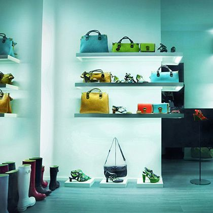 turquoise illuminated fashion store showing shoes and bags