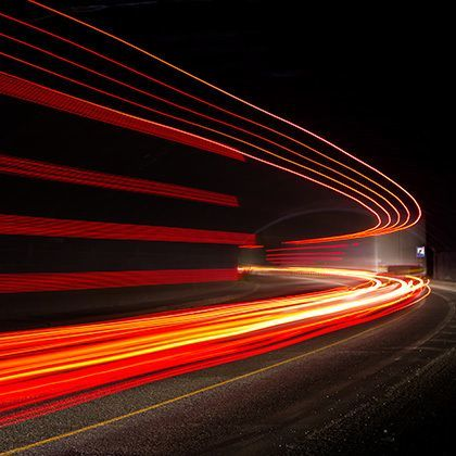 long exposure photo of truck light trails in tunnel