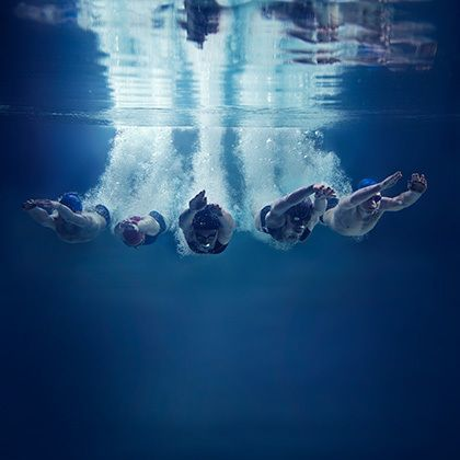 five swimmers jumping together into water