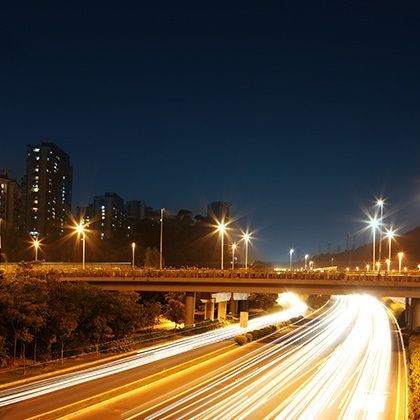 long exposure photograph of highway at night with bright traffic light