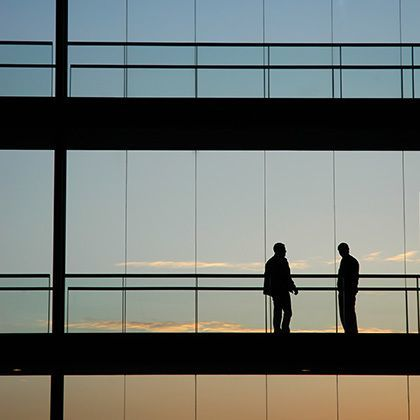 silhouettes of two men standing and watching sunset