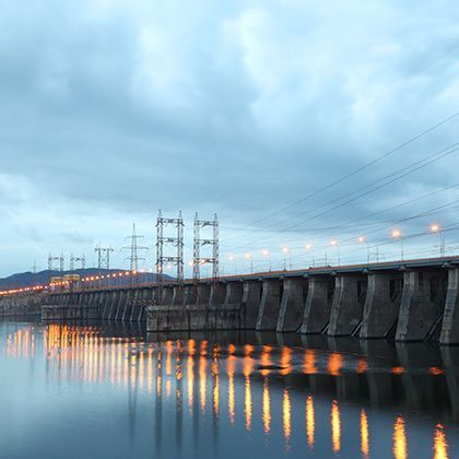 hydroelectric power station at cloudy evening, posts with high-voltage wires