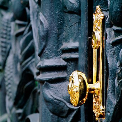 golden doorknob on cast-iron gate