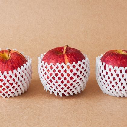 group of red apples with protective packaging on paper background
