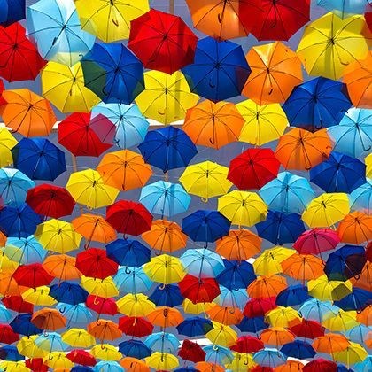 lots of umbrellas colouring the skye in the city of agueda, portugal
