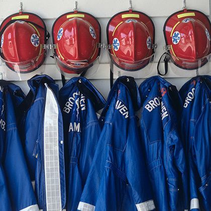 closeup of fire fighter's helmets and fire protective suits haning on hooks