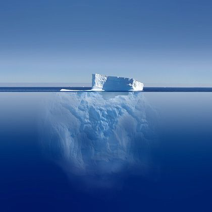 view at transparent water with partly under water iceberg in deep blue ocean 的照片