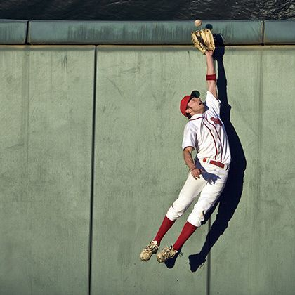 baseball player making leaping catch at wall