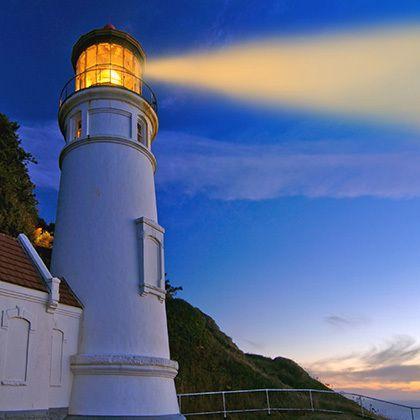 lighthouse at night with orange beam enhanced
