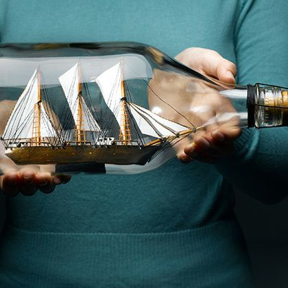 woman holding a sailing ship in bottle