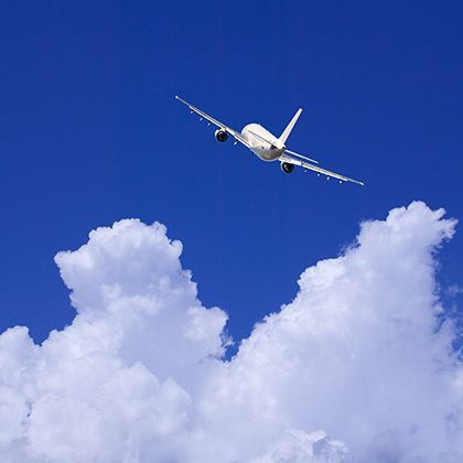 an airplane flying in the blue sky over the clouds