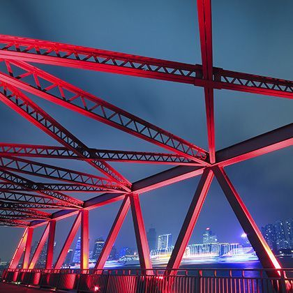 red steel structure bridge closeup at night against dark blue sky