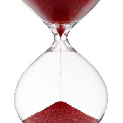 hourglass filled with red sand running down