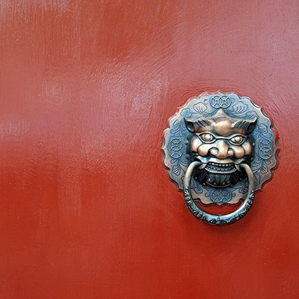 chinese vintage lion on red door 的照片