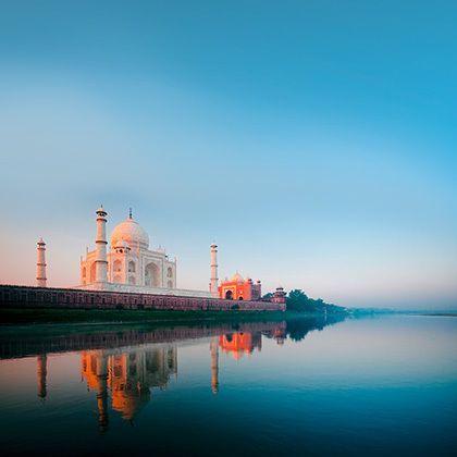 a beautiful sunrise lights the side of the taj mahal, reflecting on water