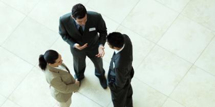 three people standing having a conversation