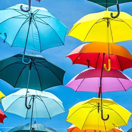 Multicoloured umbrellas against a blue sky