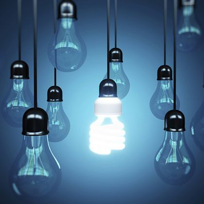 lightbulbs hanging on strings in front of a blue wall