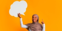 Joyful woman in hijab holding speech bubble